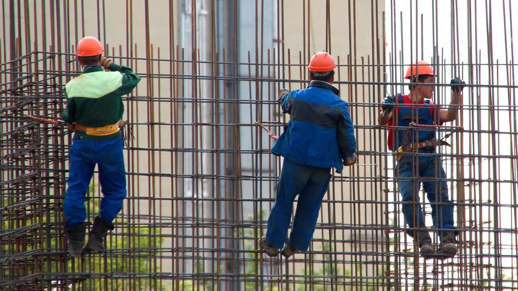 Treballadors de la construcció penjats en uns ferros